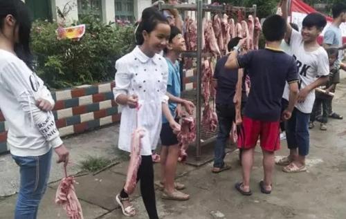 Mỗi học sinh giỏi nhận được bằng khen và 600g thịt lợn. Ảnh: SCMP