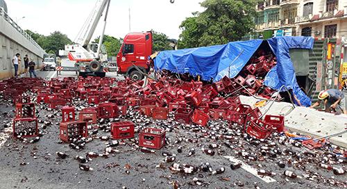 Hàng vạn chai bia đổ tràn ra đường sau vụ lật xe đầu kéo. Ảnh: Lam Sơn.