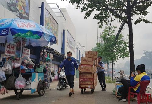 Nhân viên siêu thị kéo hàng hóa di dời. Ản:Sơn Hòa