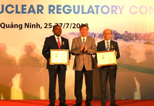 Thứ trưởng Phạm Công Tạc (giữa) trao Kỷ niệm chương vì sự nghiệp khoa học và công nghệcho các chuyên gia quốc tế. Ảnh: Thu Hiền.