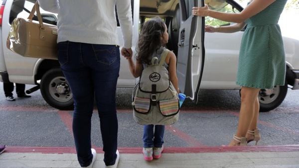Immigrants seeking asylum Natalia Oliveira da Silva, left, and her daughter, Sara, 5, wait to board a van at a Catholic Charities facility in San Antonio on July 23, 2018. Since their separation in late May, the girl had been at a shelter for immigrant minors in Chicago, while Oliveira was taken to various facilities across Texas. (Eric Gay / AP)