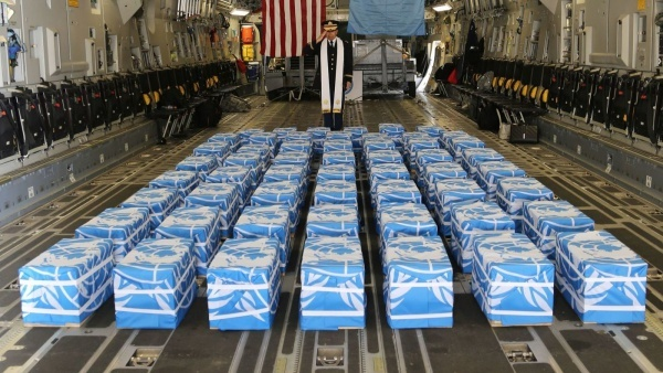 A U.S. Army chaplain, Col. Sam Lee, blesses 55 cases of remains returned by North Korea at Osan Air Base in Pyeongtaek, South Korea, on July 27. (Quince Lanford / U.S. Defense Department)