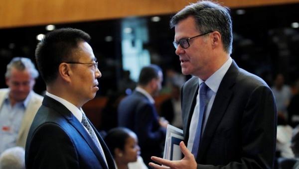 Đại sứ Mỹ và Trung Quốc tại WTO thảo luận trước cuộc họp. Ảnh: Reuters.