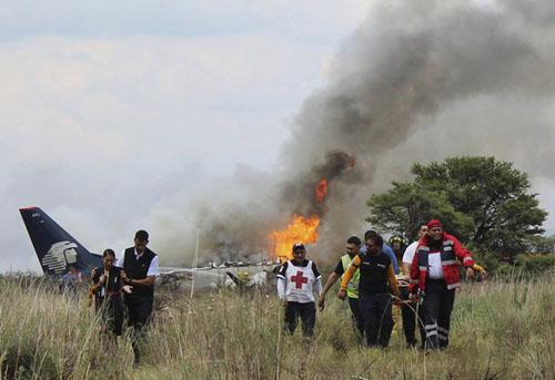 Nhân viên cứu hộ đưa người bị thương khỏi hiện trường máy bay Mexico gặp nạn. Ảnh: Reuters.