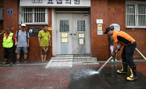 Một lính cứu hỏa xịt nước làm mát hẻm trong khu dân cư ở Seoul. Ảnh: AFP.