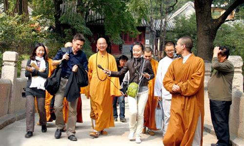 Thích Học Thành (giữa) trong một lần tiếp đón khách nước ngoài tại chùa Long Tuyền. Ảnh: Baidu.