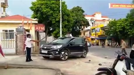 Người đàn ông được cho là bảo vệ của Ngân hàng Agribank chi nhánh huyện Hưng Hà (Thái Bình) cầm kiếm đập phá chiếc xe ô tô CRV của một phụ nữ để gần cổng trụ sở ngân hàng vào chiều 3/8. Ảnh: cắt từ video clip