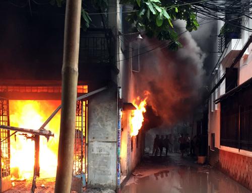 Căn nhà bốc cháy ngùn ngụt trong cơn mưa. Ảnh:Tin Tin