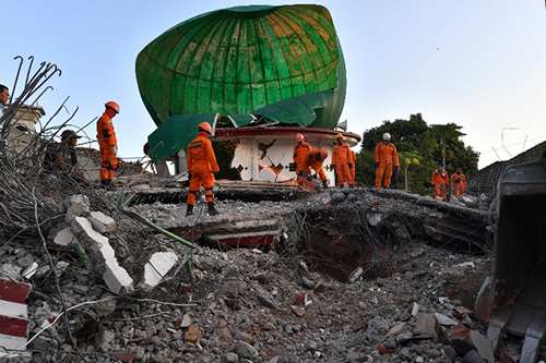 [Caption]ndonesian search and rescue personnel work on a collapsed mosque in Pemenang, North Lombok on August 6,