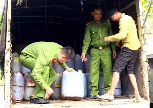 Cảnh sát kiểm tra các can dầu ăn đã qua sử dụng trên ôtô tải. Ảnh: Nguyễn Hằng.