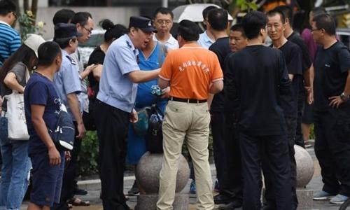 Cảnh sát nói chuyện với người biểu tình tại Bắc Kinh ngày 6/8. Ảnh: AFP.