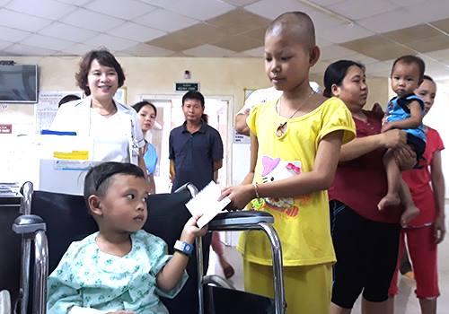 Em Tiến (ngồi xe lăn) trao quà hỗ trợ cho các bệnh nhi nghèo. Ảnh: X.D.