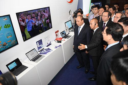 Thủ tướng Nguyễn Xuân Phúc và lãnh đạo các bộ, ngành, doanh nghiệp tham quan gian hàng tại Diễn đàn cấp cao công nghiệp 4.0 tổ chức ngày 13/7 tại Hà Nội. Ảnh: Giang Huy.