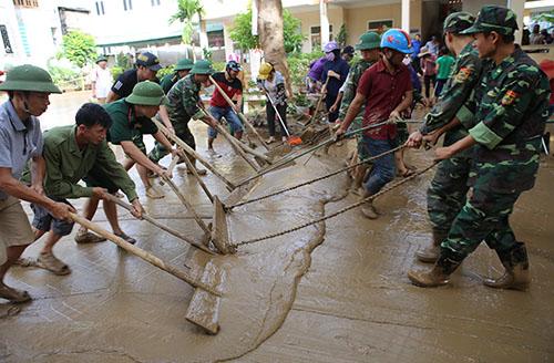 Phụ huynh, giáo viên cùng cùng lực lượng chức năng thu dọn bùn tại trường Tiểu học thị trấn Mường Xén (Kỳ Sơn) sáng 19/8. Ảnh: Nguyễn Hải.