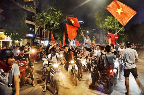 Cổ động viên ở Hà Nội đi xe máy thành từng đoàn, dừng lại, hát vang bài ca Nối vòng tay lớn sau chiến thắng của đội tuyển Việt Nam gặp Bahrain hôm 23/8.Ảnh: Giang Huy