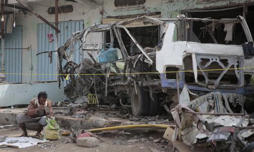 Một người thu nhặt mảnh vụn từ xác xe buýt trúng bom hôm 9/8. Ảnh: Reuters.