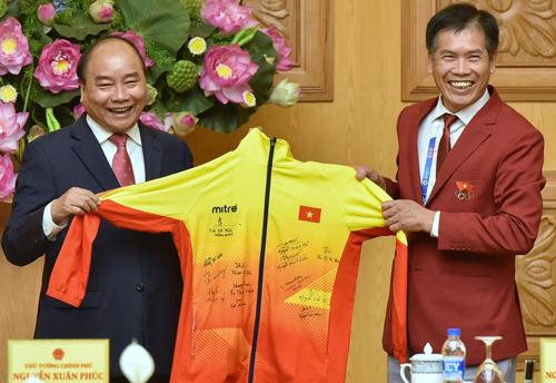 Thủ tướng Nguyễn Xuân Phúc nhận chiếc áo có chữ ký của các vận động viên đoạt huy chương vàng Asiad 18. Ảnh: Giang Huy.