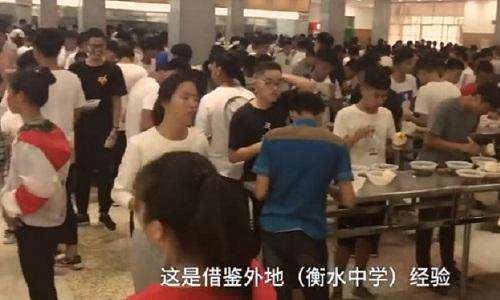 Học sinh phải đứng ăn trong canteen để tiết kiệm thời gian dành cho việc học. Ảnh: Pear Video