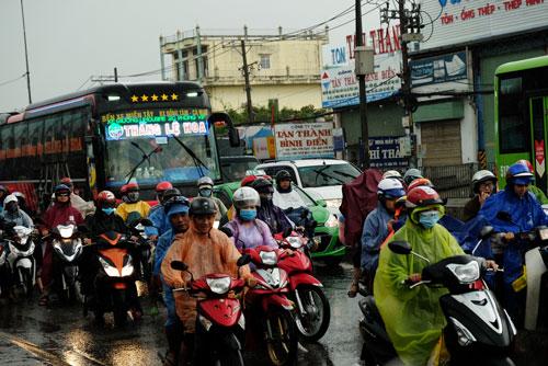 Người dân từ các tỉnh miền Tây đội mưa trở lại Sài Gòn chiều nay. Ảnh: Mạnh Tùng