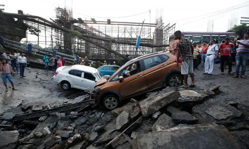 Các phương tiện rơi xuống trong vụ sập cầu tại thành phố Kolkata, Ấn Độ vào hôm qua. Ảnh: Reuters.