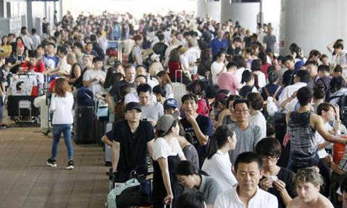 Hàng nghìn người xếp hàng chờ xe buýt rời khỏisân bay Kansai sáng nay. Ảnh: iTv.