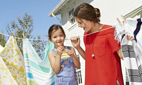 Giặt quần áo là kỹ năng trẻ cần học sớm. Ảnh: Parents