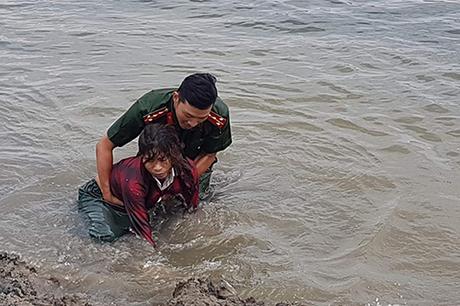 Đại uý Thế dìu người phụ nữ cào hến vào bờ. Ảnh: Công an Quảng Bình