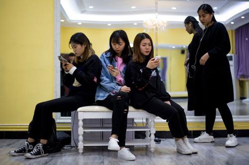 Sinh viên Đại học Công nghiệp và Thương mại Nghĩa Ô, Trung Quốc sử dụng điện thoại để vào mạng xã hội. Ảnh: AFP.