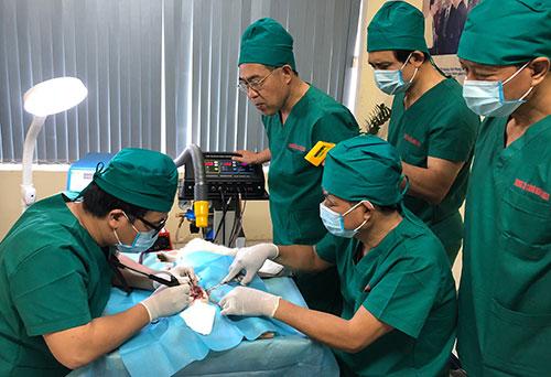 Bác sĩ Đỗ Tuấn Anh (bìa trái) và nhóm nghiên cứu thực nghiệm thiết bị trên mô sống của thỏ. Ảnh: BN.