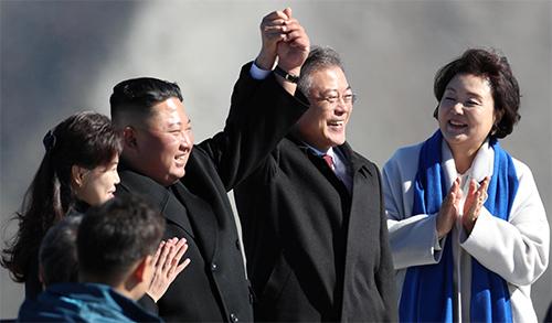Lãnh đạo Triều Tiên Kim Jong-un và Tổng thống Hàn Quốc Moon Jae-in nắm tay khilên đến đỉnh núi Paektu sáng nay. Ảnh: Reuters.