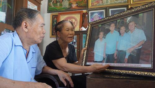 Vợ chồng thầy Lê Kim Toàn ngắm bức ảnhchụp cùng Chủ tịch nước Trần Đại Quang trongdịpngười học trò cũ về thăm quê năm 2016.Ảnh: Lê Hoàng.