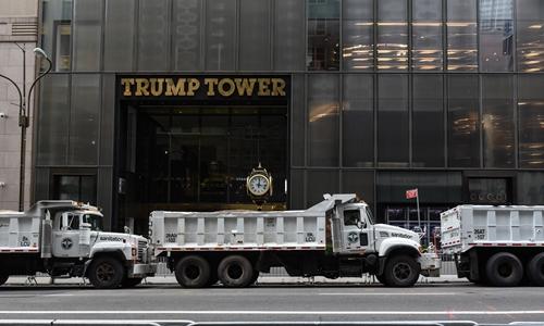 Xe tải chứa cát được bố trí làm hàng rào an ninh trước tháp Trump. Ảnh: Reuters.