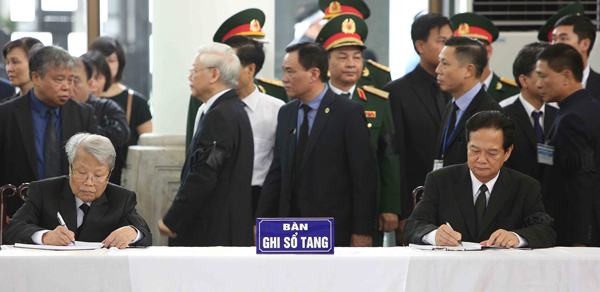 Từ trái qua: Nguyên Chủ tịch nước Trần Đức Lương, nguyên Thủ tướng Nguyễn Tấn Dũng ghi sổ tang. Ảnh: TTX