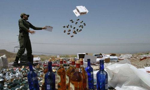 Một binh sĩ Iran tiêu hủy rượu bia trái phép năm 2015. Ảnh: AP.