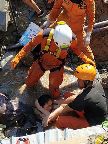 Các nhân viên cứu hộ giải cứu Nurul Istikharah hôm qua. Ảnh: Reuters