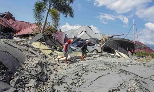 Người dân bước trên con đường bị phá hủy tại thành phố Palu, tỉnh Trung Sulawesi sau khi động đất và sóng thần tàn phá khu vực này. Ảnh: Reuters.