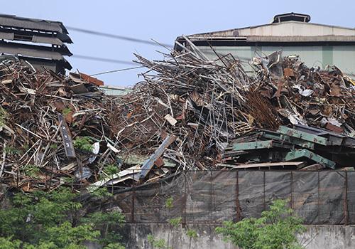 Hàng tấn phế liệu ngay cạnh tường rào nhà máy thép giáp với khu dân cư. Ảnh: Nguyễn Đông.