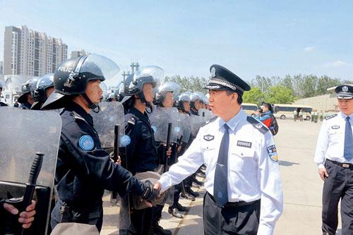 Mạnh Hoành Vĩ (thứ hai từ phải sang) bắt tay cảnh sát Trung Quốc chuẩn bị thực hiện nhiệm vụ gìn giữ hòa bình ở Liberia năm 2014. Ảnh: ChinaPictoral.