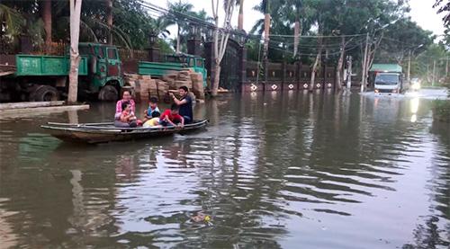 Ngập sâu, người dân lấy xuồng bơi trên lộ ở một khu dân cư mới tại quận trung tâm Ninh Kiều. Ảnh: Hồng Thắm