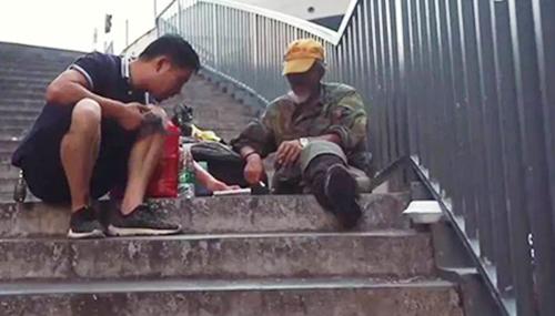 Cai Yanqiu trò chuyện với một người vô gia cư. Ảnh: Peoples Daily
