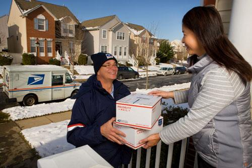 Nhân viên USPS (trái) chuyển bưu kiện tới khách hàng. Ảnh: KoreanTimes.