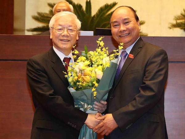 Thủ tướng Nguyễn Xuân Phúc tặng hoa chúc mừng Tổng bí thư, Chủ tịch nước Nguyễn Phú Trọng. Ảnh: TTX