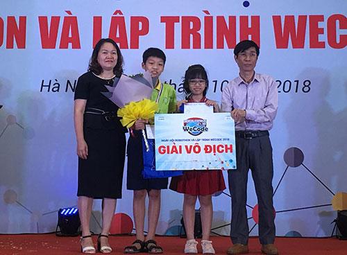 Ông Nguyễn Trung Quỳnh, Phó trưởng ban Quản lý khu Công nghệ cao Hòa Lạc trao giải vô địch lập trình mức độ sơ cấp cho em Nguyễn Linh Anh. Ảnh: