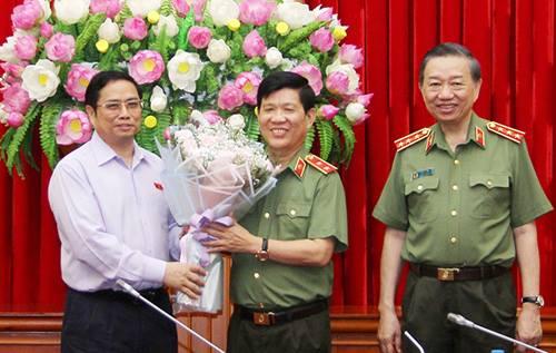 Trung tướng Sơn (đứng giữa) nhận hoa từ ông Phạm Minh Chính, Trưởng Ban Tổ chức Trung ương. Ảnh: Bộ Công an