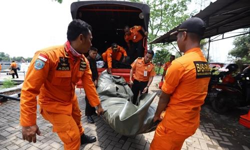 Nhân viên cứu hộ đưa thi thể nạn nhân vụ rơi máy bay lên bờ. Ảnh: AFP.