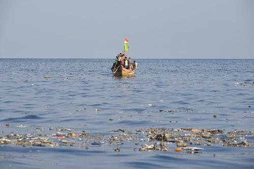 Tàu cá của ngư dân Indonesia di chuyểngần những mảnh rác trôi nổi từ máy bay gặp nạn của Lion Air trên biển Java. Ảnh: AFP