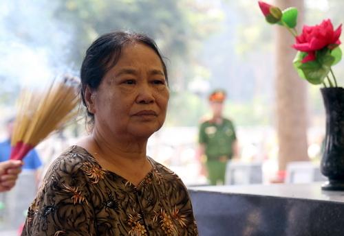 Bà Trần Thị Nga trầm ngâm phút giây an táng 13 liệt sĩ, trong đó có hài cốt chồng mình. Ảnh: Phước Tuấn