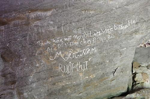 Câu khẩu hiệu trên vách đá trong hang Xưởng rượu. Ảnh: Hoàng Táo
