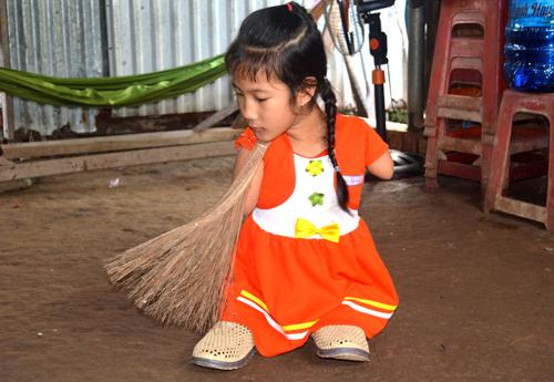 Thảo giúp bà quét nhà ngoài giờ học. Ảnh: Phúc Hưng.