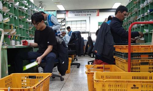 Nhân viên của Cơ quan Bưu chính Hàn Quốc phân loại bưu kiện và thư từ. Ảnh: CNN.